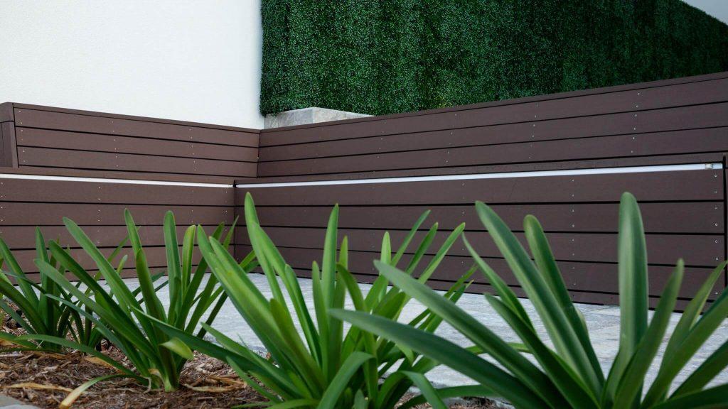 Artificial boxwood panels along an outdoor bench