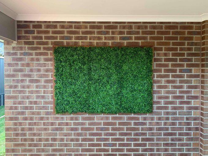 fake hedge panels installed onto brick