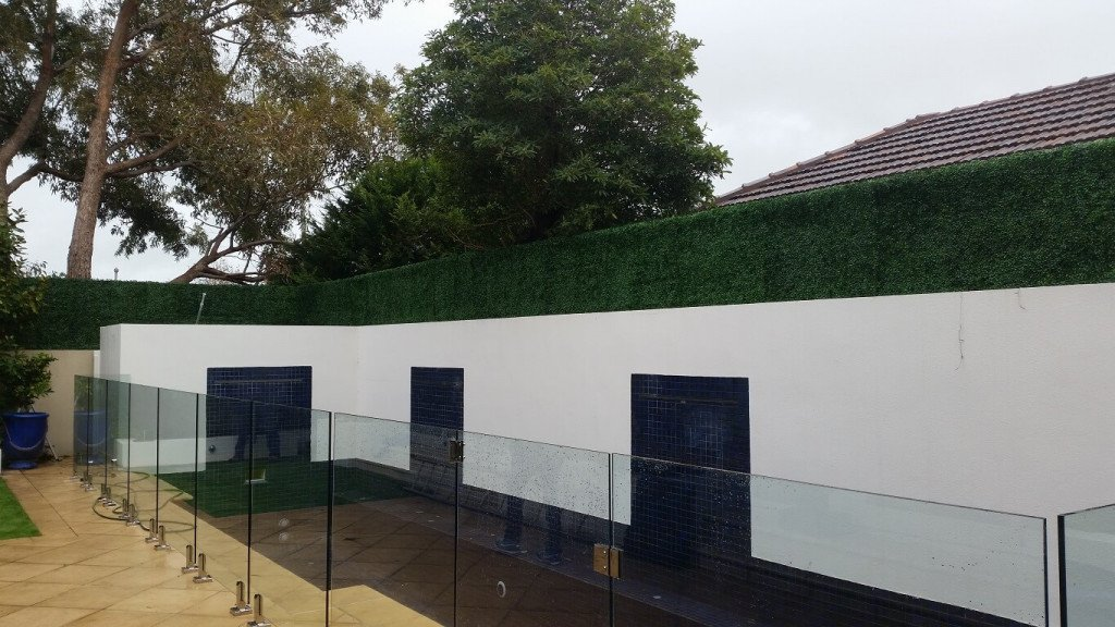 artificial boxwood fake hedge panels installed on a fence trellis