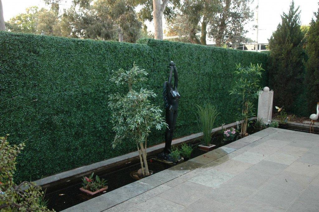 fake boxwood hedge panels installed onto a fence