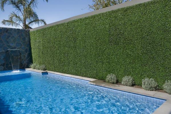 fake boxwood hedge panels near a pool